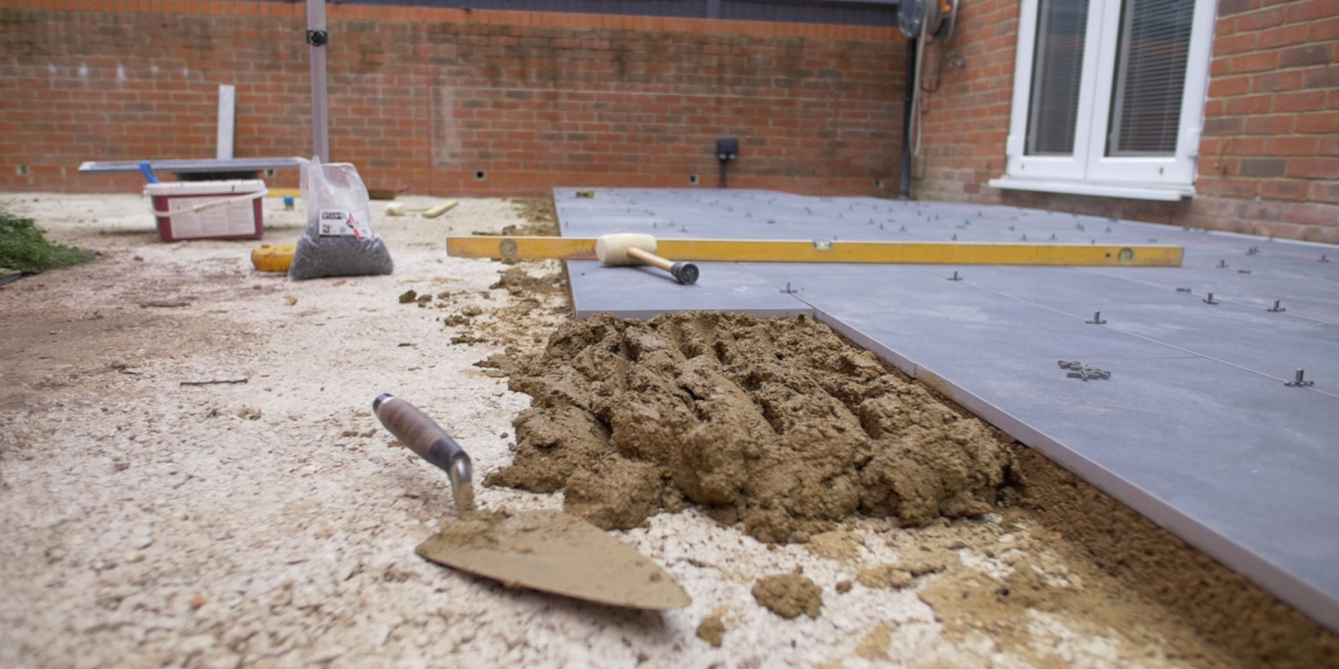 A PQC with mortar ready to lay the next porcelain slab